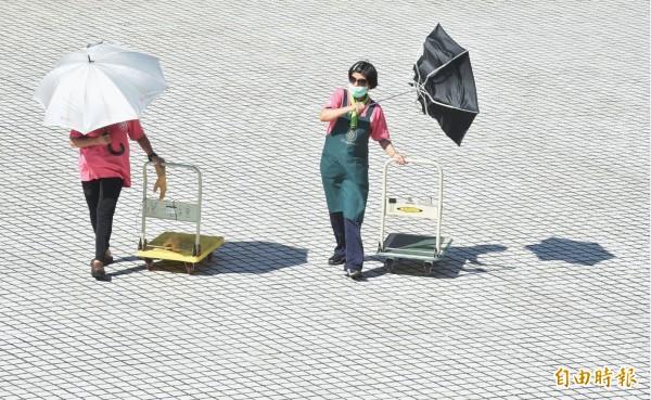 熱熱熱!台北飆至38.7度,民眾外出除了撐著陽傘,還戴上墨鏡躲避烈日。(記者劉信德攝)