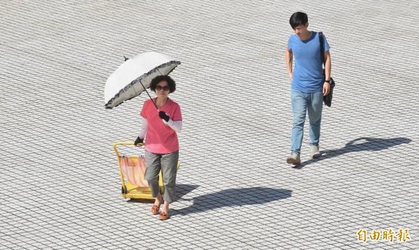 熱熱熱!台北飆至38.7度,民眾外出除了撐著陽傘,還戴上墨鏡、穿上防曬袖套躲避烈日。(記者劉信德攝)