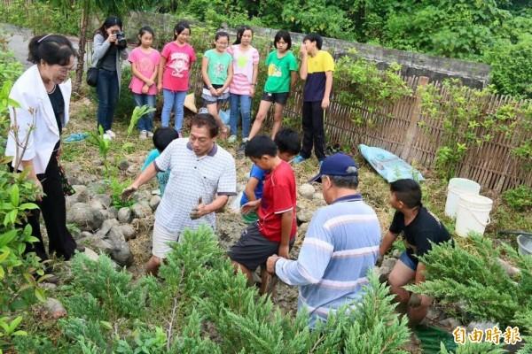 社區中的老老少少一起玩泥巴,用「土角」蓋房子。(記者詹士弘攝)