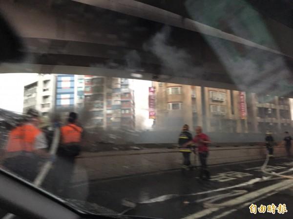 麥帥二橋下方小貨車起火,消防人員站在對向車道由上往下滅火。(記者陳宜豐攝)
