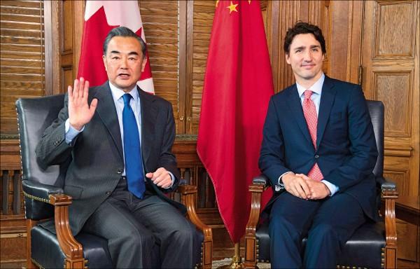 加拿大總理杜魯道(右)一日在國會接見中國外交部長王毅(左)。(美聯社)