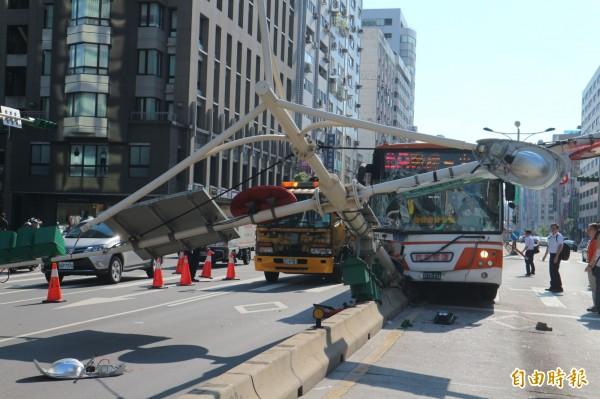 公車硬生生撞倒交通號誌桿。(記者陳薏云攝)