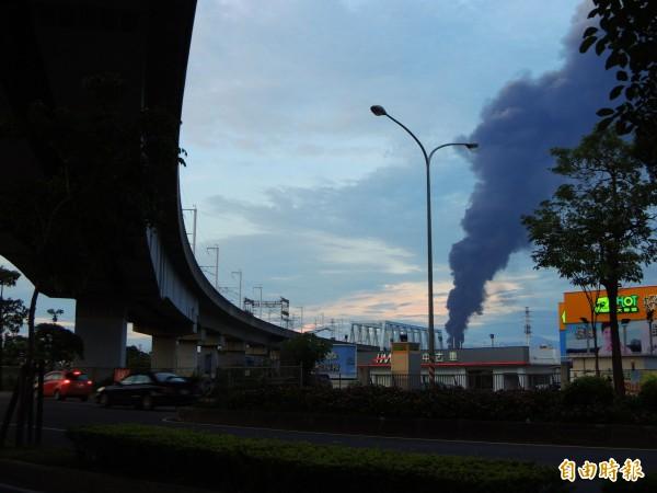 高鐵左營站附近資源回收場發生火警,濃煙從高鐵軌道(左)旁竄出。(記者黃旭磊攝)