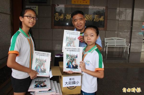 彰化大莊國小校長張樹閔(右2)與畢業生開心的領回校史第1本畢業紀念冊。(記者陳冠備攝)
