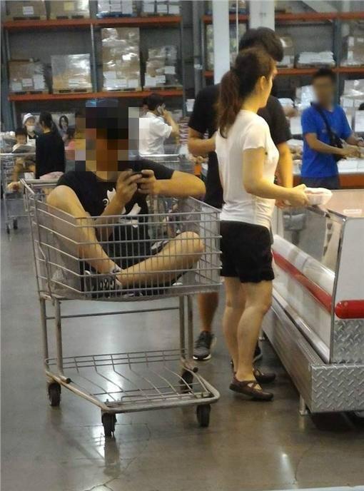 一名年輕男子不顧他人眼光,大喇喇的坐在手推車裡滑手機,一旁的婦人也不以為意,看著架上的物品沒有任何勸阻的行為。(圖擷自爆料公社)