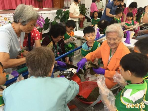 中華國小附幼小朋友前往中山區通明里活動中心,阿嬤展示熟練的包粽技巧,小孩子大嘆神奇。(記者俞肇福攝)