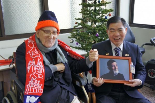 來台傳道服務超過半世紀的施予仁神父(左)6日長眠台灣,圖為2011年時任移民署副署長的何榮村(右),拿著神父50多歲時的照片探望他。(圖由移民署提供)