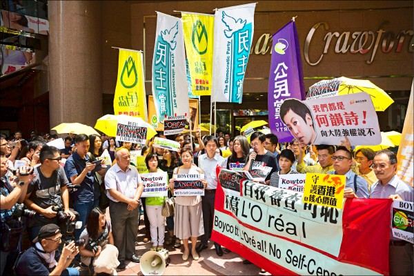 香港泛民主派人士八日在銅鑼灣時 代廣場外示威,抗議萊雅旗下品牌蘭 蔻為了中國市場,取消與支持香港民 運的藝人何韻詩合作。 (歐新社)