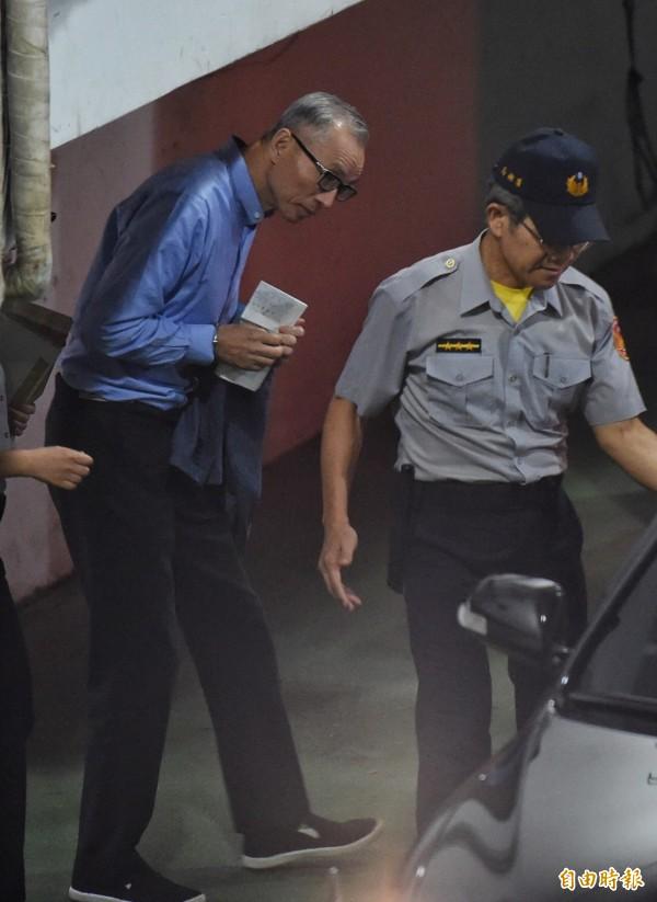 國寶集團總裁朱國榮(左)遭裁定羈押禁見,由法警戒護送上囚車。(記者劉信德攝)