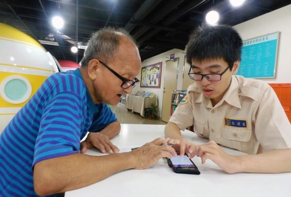 蘆洲長安分館替代役張偉豪(右)悉心教導阿公使用智慧型手機。(新北市立圖書館提供)