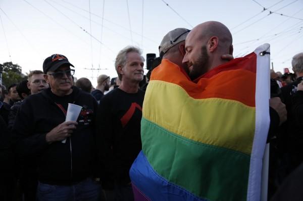 一對同志情侶在哈維米克廣場包裹著彩虹旗幟相擁。(歐新社)
