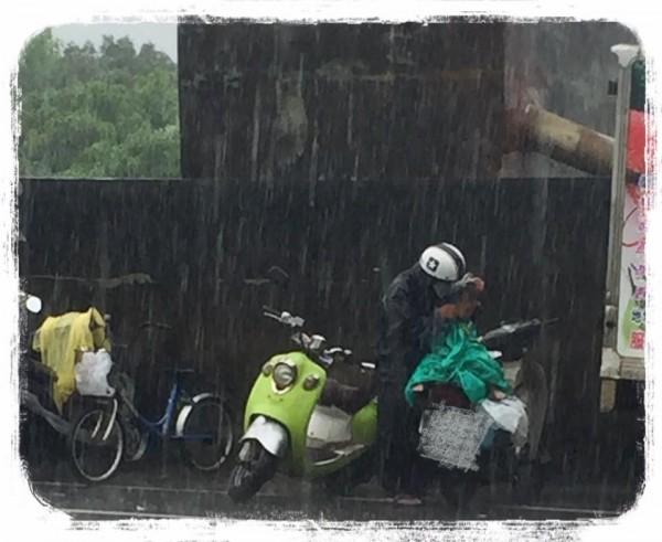 蕭姓民眾把這張爺孫冒雨領剩食的照片傳到臉書,引起社會廣大迴響。(記者黃佳琳翻攝)