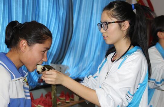 圖為一名漢族學生餵維吾爾族學生吃粽子。(圖擷自《自由亞洲廣播電台》)