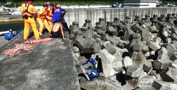 海巡人員逐一將受困的香港潛水客拉上岸。(記者陳賢義翻攝)