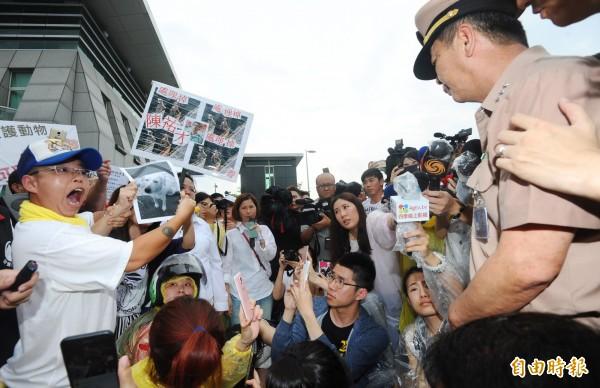 動保人士28日赴國防部抗議虐狗事件,拿出小白照片,痛責出面道歉的海軍司令黃曙光(右)。(記者張嘉明攝)