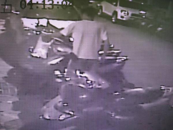 林男(白衣者)將燒餘香環丟棄在住家對面的機車置物籃內,竟不慎燒毀8輛車。(記者陳薏云翻攝)