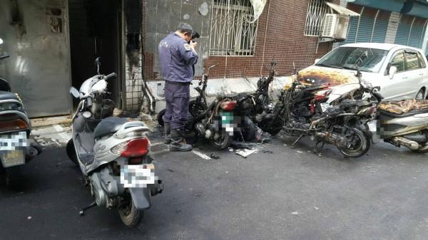 林男將燒餘香環丟棄在住家對面的機車置物籃內,竟不慎燒毀8輛車,警方到場採證。(記者陳薏云翻攝)
