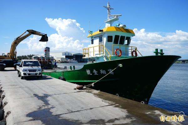 東硫碼頭的貨船正待怪手吊掛水塔上船。(記者陳彥廷攝)