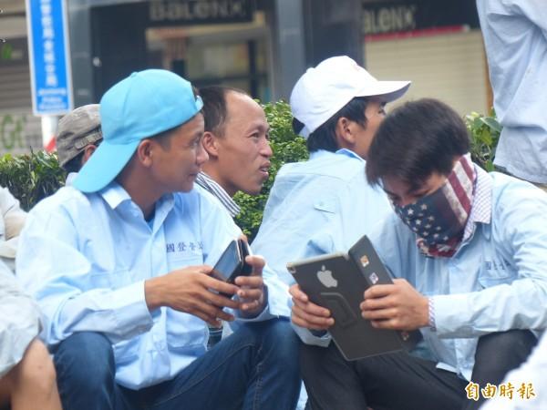 越南籍外勞在縣府前靜坐,藉平板電腦打發時間。(記者吳正庭攝)