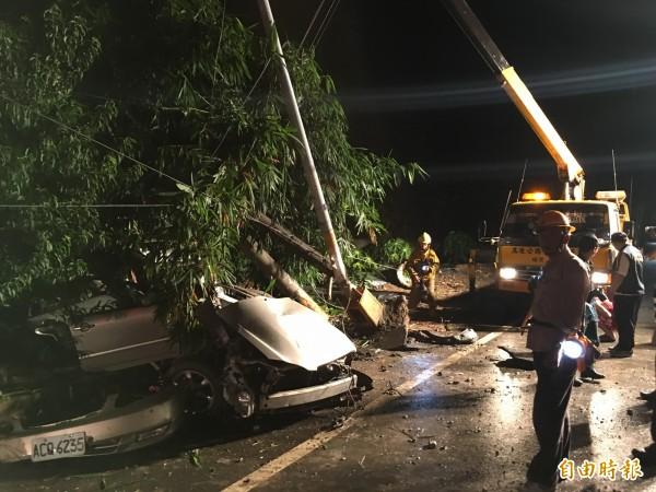 撞擊力道猛烈電線桿及路燈斷裂,自小客車也嚴重扭曲變形。(記者黃淑莉攝)