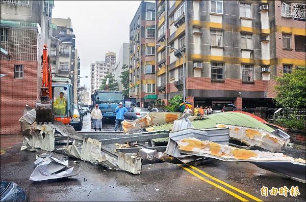 屏東多處招牌、鐵皮屋頂被吹落,市公所工程人員調來怪手清除鐵皮屋,恢復道路通行。(記者葉永騫攝)