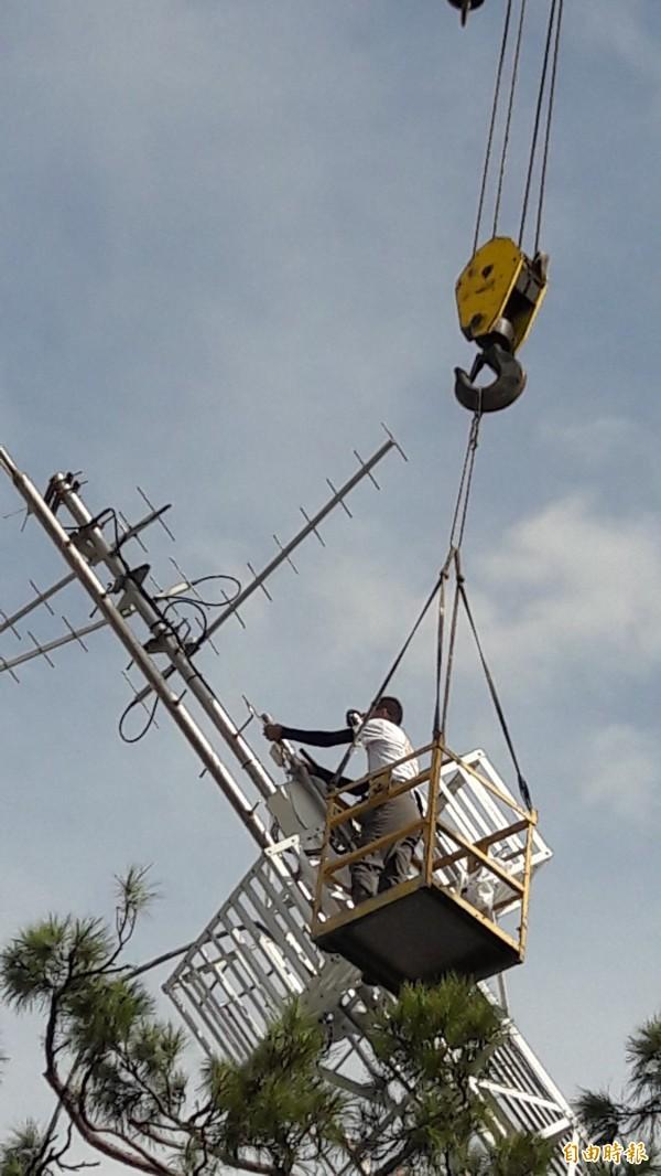 工作人員搭吊車上塔頂卸除風力儀及雨量接收器(記者黃明堂攝)