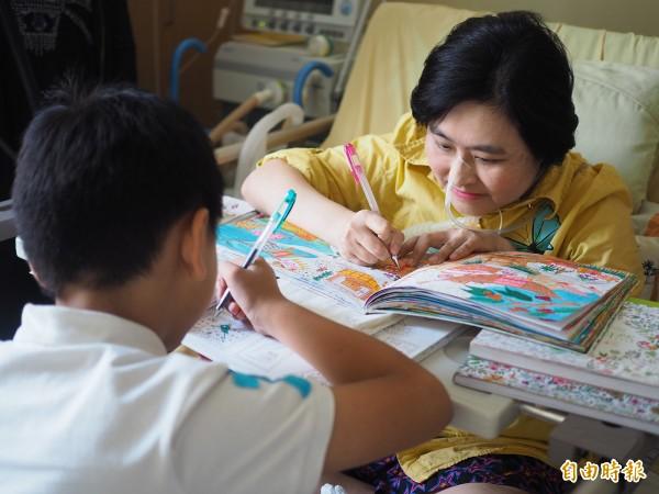 范秋英(右)投入繪畫的世界後,精神和心情都好轉,國小二年級的兒子張小弟(左)暑假幾乎每天都到病房陪她畫畫。 (記者陳昀攝)