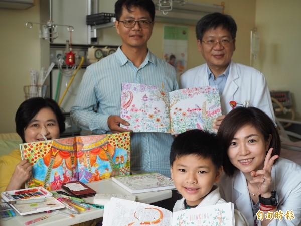范秋英(左1)投入繪畫的世界後心情和精神都變好,丈夫張涌鼒(左2)幾乎每天都帶國小二年級的兒子張小弟(前)到病房陪她畫畫。(記者陳昀攝)