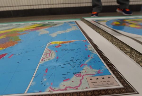 常設仲裁法院今天將會就南海主權爭議作出裁決。圖為中國北京街頭攤商販賣的地圖,其中南海諸島圖中明顯標有引發爭議的九段線。(法新社)