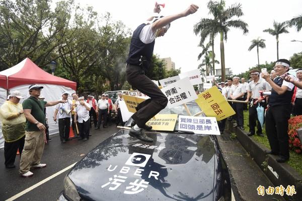 上百輛計程車的司機串聯到立法院抗議,並怒砸寫有Uber字樣的車輛。(資料照,記者陳志曲攝)