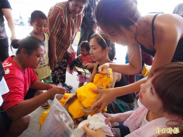 帶著物資前進部落的年輕女性協助部落婦女挑選適合小朋友的衣物。(記者王秀亭攝)