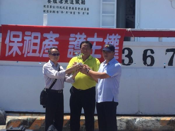 「南海行動聯盟」代表詹澈(左)將泥土和樹苗交給護漁行動召集人鄭春忠與海巡署官員。(圖由南海行動聯盟提供)