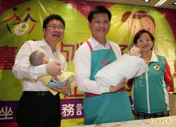 台中市長林佳龍(中)、社會局長呂建德客串坐月子服務人員,示範如何照顧嬰兒。(記者張菁雅攝)