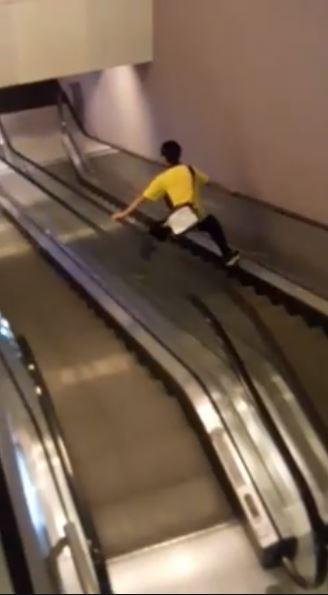 高雄市苓雅區百貨公司內的附設電影院,今天出現一位男學生以「蜘蛛人」的姿勢搭乘電扶梯,讓網友笑稱「長痔瘡嗎?」。(圖擷取自影片)