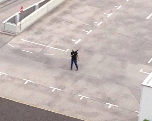 疑似槍擊案現場的影片中,穿著黑衣的槍手在停車場頂樓,與他人發生爭執,並宣稱「我是德國人」。(圖片擷取自推特)
