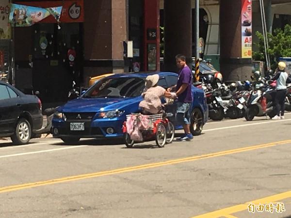 賣菜阿婆鎖定一名男子,要求其購買三輪車上的蔬菜。(記者鄭鴻達攝)