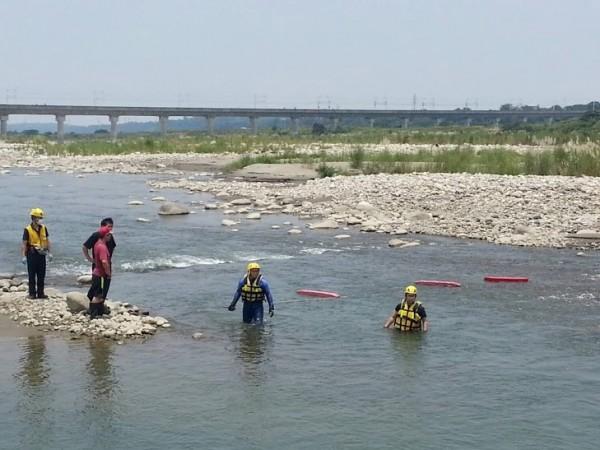 消防人員在大甲溪中搜尋溺水的男子。(記者歐素美翻攝)