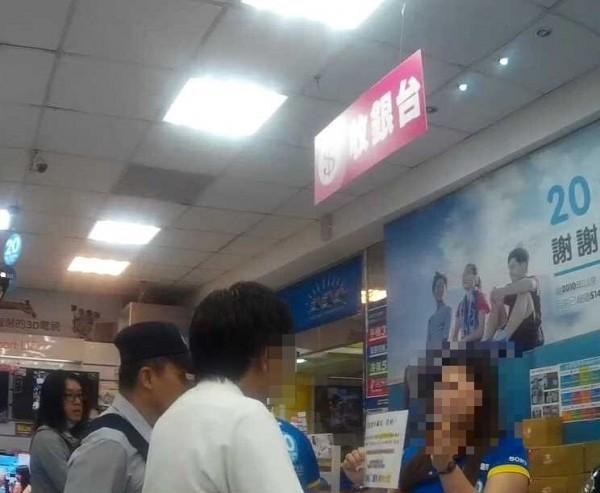 吳男(左白衣)到3C量販店買遊戲點數要付給詐騙集團,被女店員與警方聯手阻詐。(記者王俊忠翻攝)