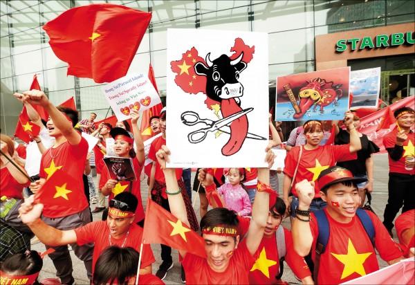 約百名越南旅韓僑民廿四日在首爾明洞的中國駐南韓大使館前,抗議中國入侵越南領海,標語牌上畫有一個牛頭伸出長長的牛舌,其實就是中國所稱的南海「九段線」,越南故意稱之為「牛舌線」,意指北京撈過界「舔到」東南亞國家外海。示威者還一度與中國觀光客對罵,但未爆發進一步衝突。(美聯社)