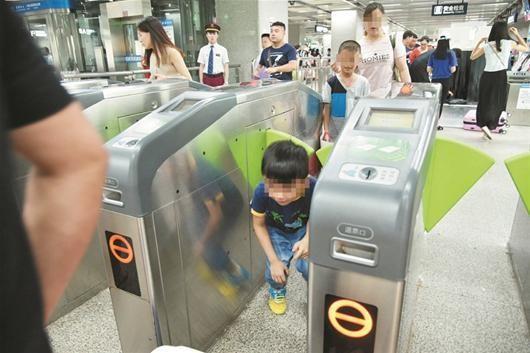 武漢地鐵逃票嚴重,有人直接鑽閘門逃票。(圖擷取自楚天都市報)