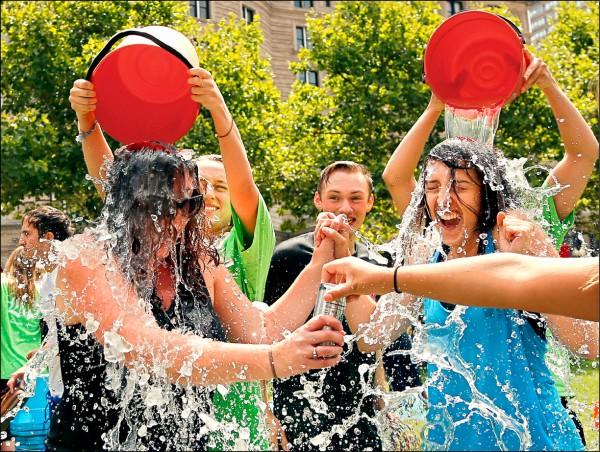 美國漸凍人症協會二十六日證實,兩年前風靡全球的公益活動「冰桶挑戰」(Ice Bucket Challenge),所募集的資金已實際資助多項有關漸凍症的研究計畫,使研究出現突破性進展。圖為兩名女子二○一四年八月在美國波士頓科普利廣場(Copley Square)參加冰桶挑戰。 (美聯社檔案照)