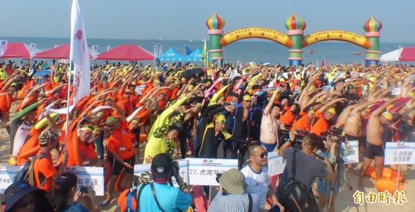 金門搶灘料羅灣逾2000人下水前暖身,把海灘烘襯的光彩、熱鬧。(記者吳正庭攝)