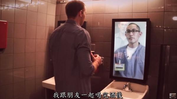 一名身穿藍衣的囚犯Kris Caudilla出現在酒吧鏡子中,與正在喝酒的酒客對話。(圖擷自YouTube)