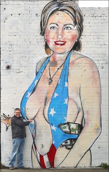 澳洲街頭塗鴉藝術家拉西薩克斯日前在墨爾本街頭創作一幅美國民主黨總統候選人希拉蕊.柯林頓身穿美國國旗泳裝的作品,過於暴露的畫面引發軒然大波,當地民意機關以該塗鴉描繪近乎裸體的女人,觸犯相關法律為由,要求牆主在十天內將該塗鴉移除。拉西薩克斯得知後怒斥撤圖要求「真可悲」,但民意機關強調,移除令與畫作描繪人物無關。圖為一名男子三十日與牆上塗鴉合影。 (法新社)