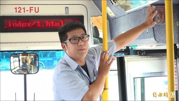 新店客運935路線公車駕駛黃昭運,講解緊急狀況時,如何操作車門上的緊急開關。(記者洪葦竹攝)