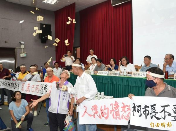 台北市長柯文哲3日出席廣慈博愛園區公宅計畫公聽會,居民撒冥紙、拉布條抗議公園遭取消。(記者方賓照攝)