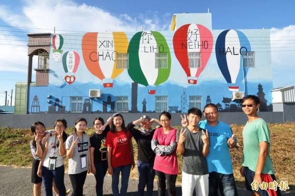 台西國際志工工作營今年主題為「跟世界說你好」,志工們在透天厝外牆畫上各國國旗的熱汽球。(記者黃淑莉攝)
