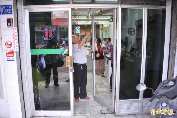 郵局檢視被撞壞的玻璃門。(記者蔡宗憲攝)