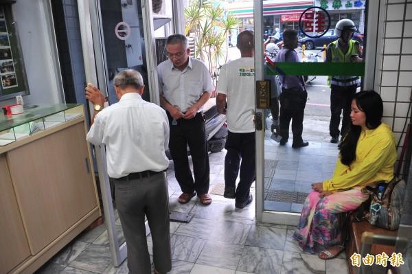 郵局檢視被撞壞的玻璃門,黃衣為肇事陳女。(記者蔡宗憲攝)