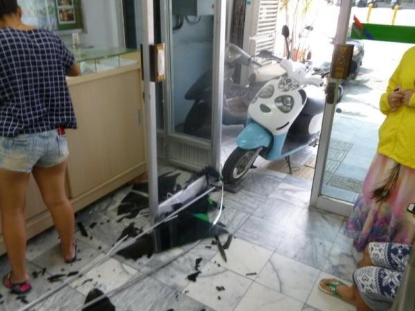 電動車衝破郵局大門。(記者蔡宗憲翻攝)